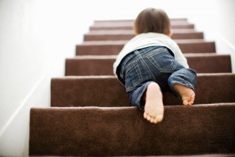 A baby crawling on the stairs